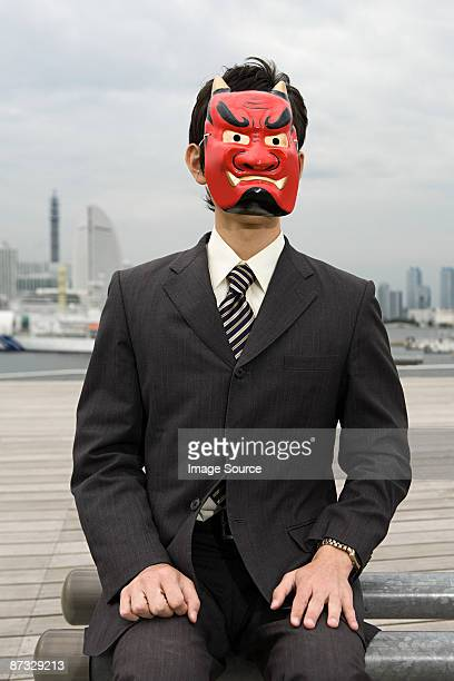 portrait of a businessman wearing a devil mask - devil costume stock photos and pictures