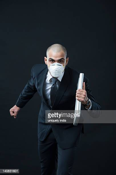 Portrait of a businessman wearing a pollution mask and running