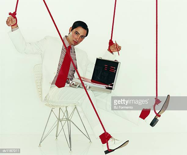 portrait of a businessman wearing a white suit sitting on a chair controlled by ropes - man tied to chair stock photos and pictures