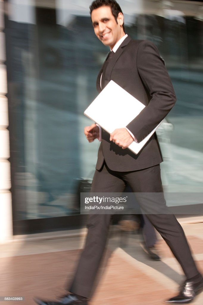 Portrait of a businessman with a laptop walking , INDIA , DELHI : Stock Photo