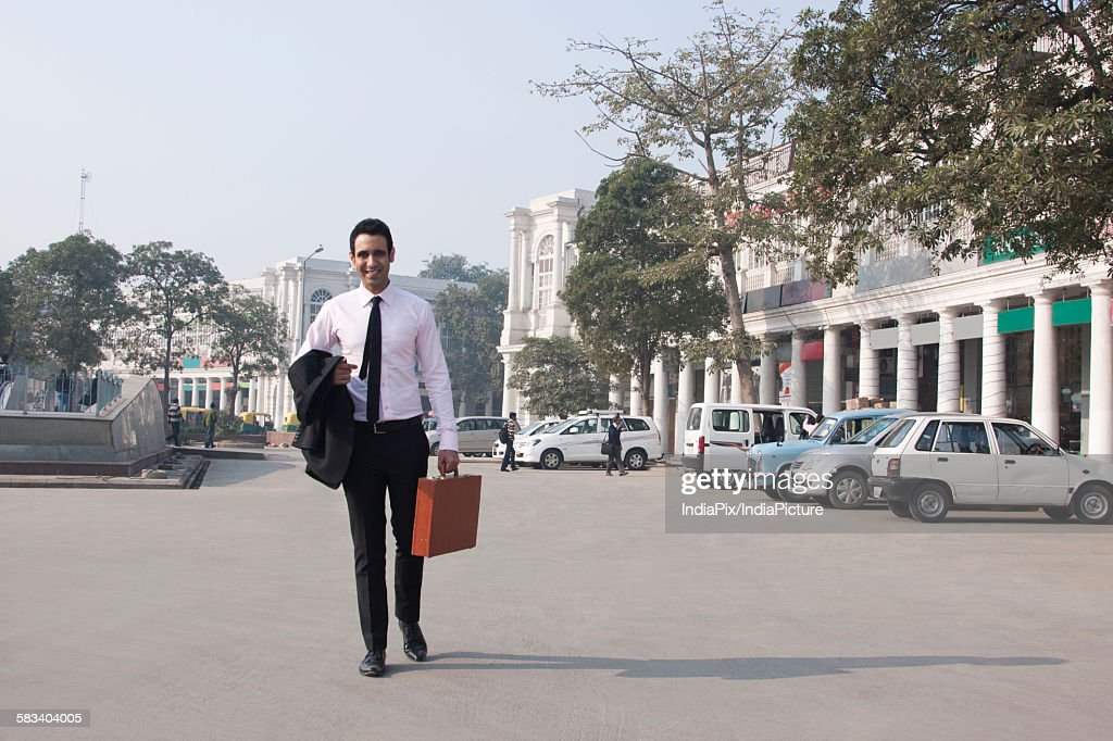 Portrait of a businessman with a suitcase walking , INDIA , DELHI : Stock Photo
