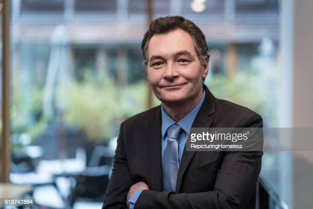 Porträt eines Geschäftsmannes der mit verschränkten Armen glücklich in die Kamera schaut