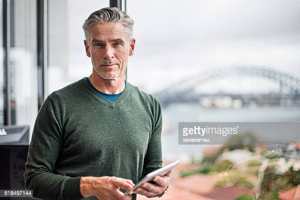 portrait of a businessman with digital tablet in office - oudere mannen stockfoto's en -beelden