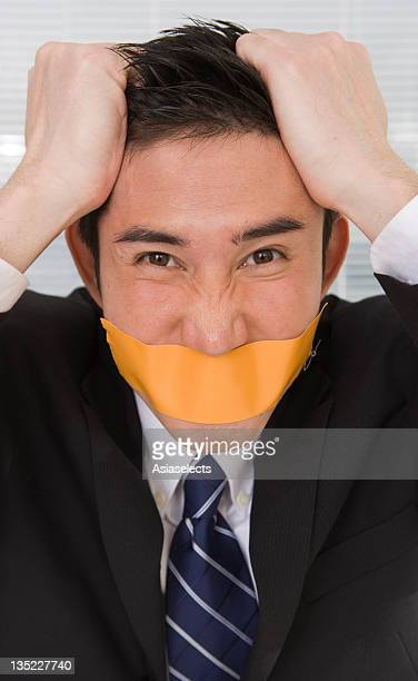 Portrait of a businessman with duct tape on his lips and pulling his hair