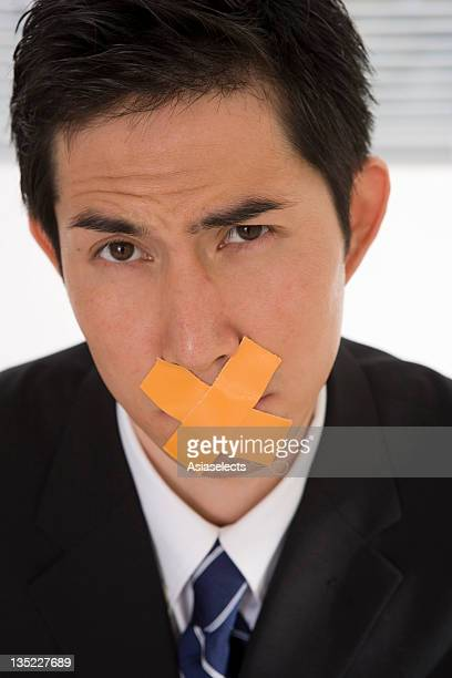 Portrait of a businessman with duct tapes on his lips