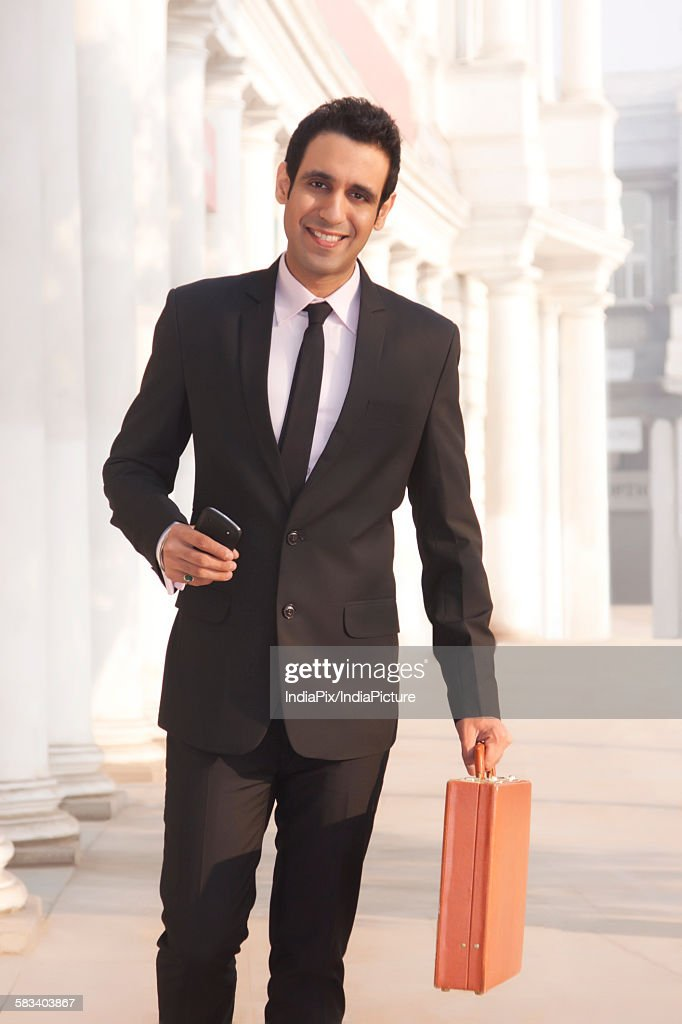 Portrait of a businessman with suitcase smiling , INDIA , DELHI : Stock Photo