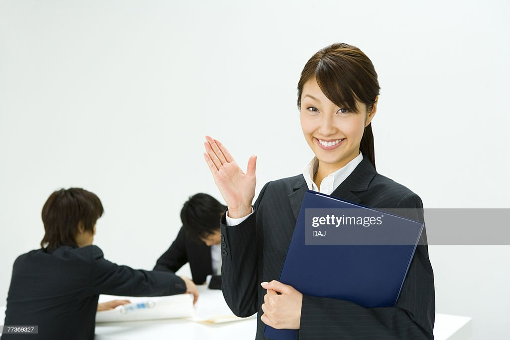 Portrait of a Businesswoman and Businessmen talking in the Background, Front View : Stock Photo
