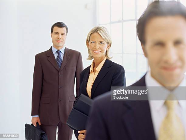 portrait of a businesswoman and two businessmen smiling