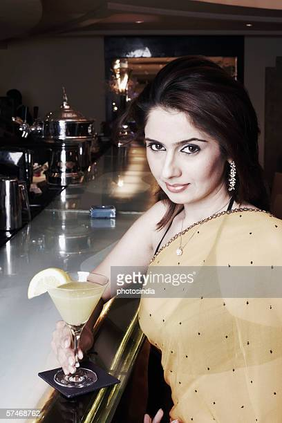 Portrait of a businesswoman at a bar counter holding a martini glass