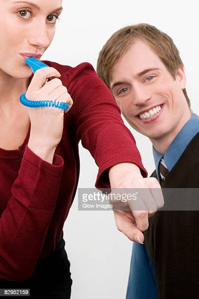 Portrait of a businesswoman blowing a whistle with a businessman standing beside her