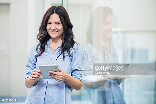 Portrait of a businesswoman carrying digital tablet in office