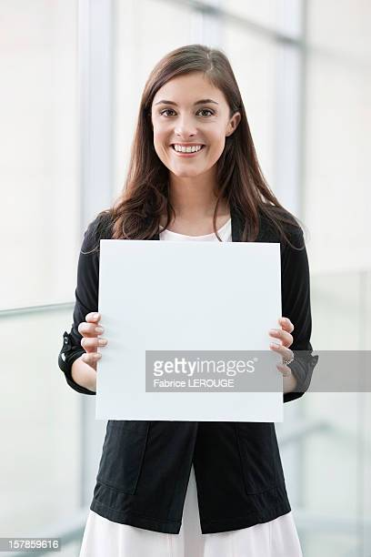 portrait of a businesswoman holding a blank placard and smiling in an office - halten stock-fotos und bilder