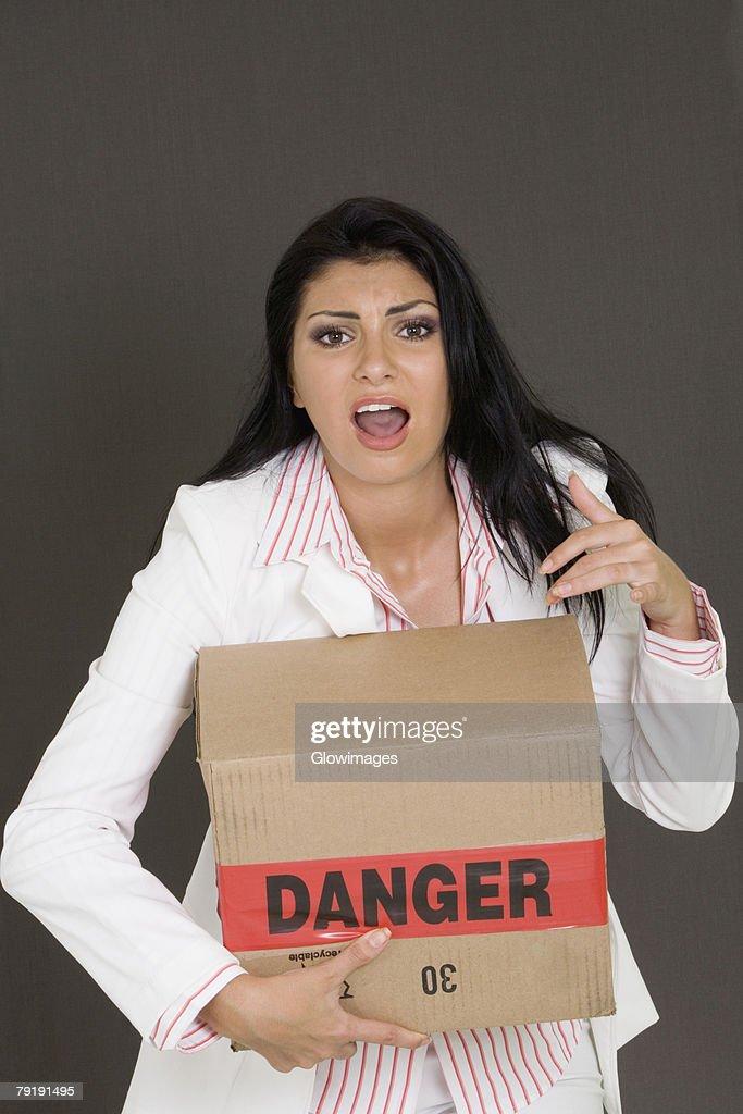 Portrait of a businesswoman holding a cardboard box : Foto de stock
