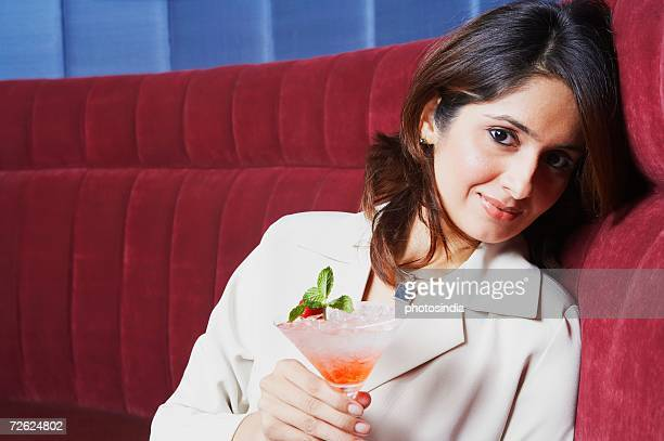 Portrait of a businesswoman holding a glass of martini