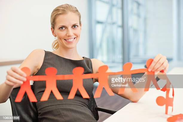 Portrait of a businesswoman holding a human paper chain