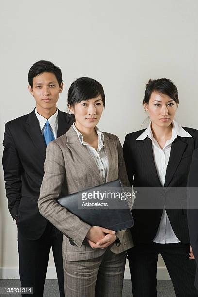 Portrait of a businesswoman holding a ring binder with two business executives standing beside her