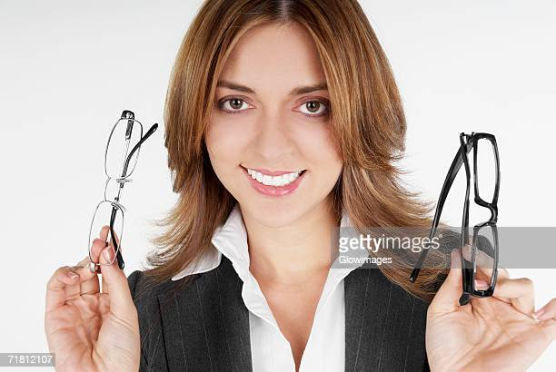 Portrait of a businesswoman holding two eyeglasses and smiling
