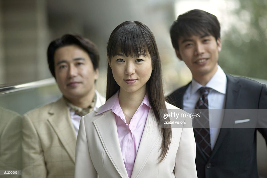 Portrait of a Businesswoman in Front of Two Businessmen : Stock Photo