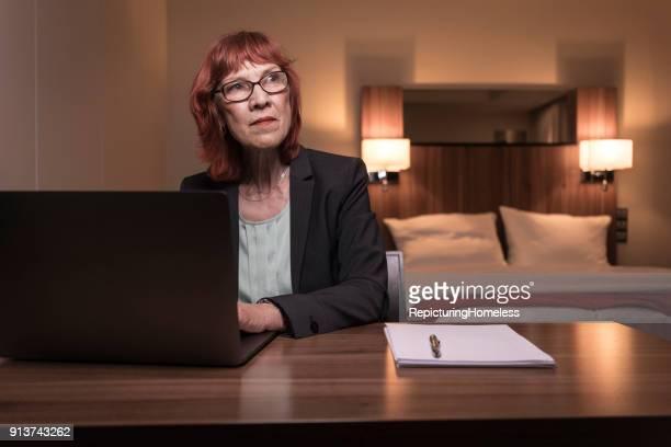 Porträt einer Geschäftsfrau die nachdenklich in ihrem Hotelzimmer sitzt