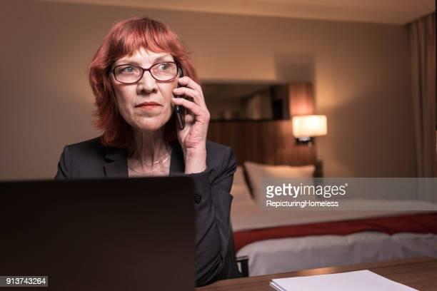 Porträt einer Geschäftsfrau die ein Telefonat in ihrem Hotelzimmer sitzt führt