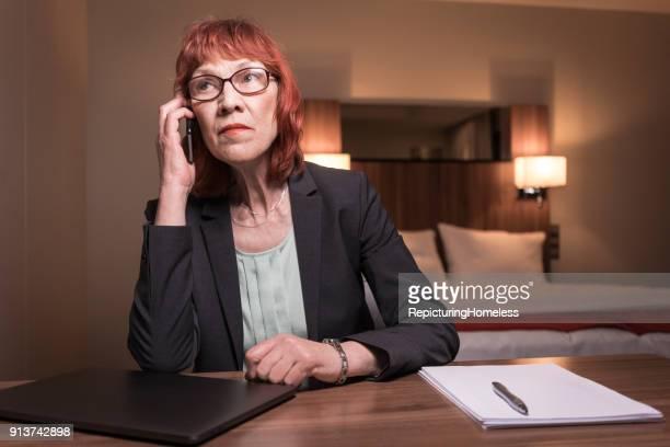 porträt einer geschäftsfrau die ein telefonat in ihrem hotelzimmer sitzt führt und nachdenklich zur seite schaut - repicturing homeless stock-fotos und bilder