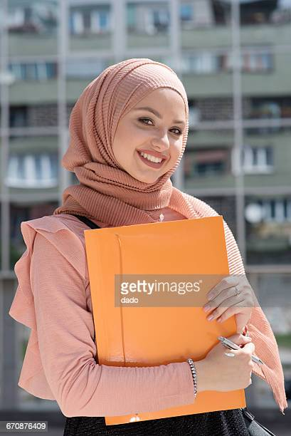 Portrait of a businesswoman in hijab holding a folder