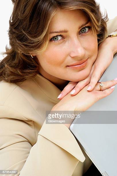 Portrait of a businesswoman leaning on a laptop