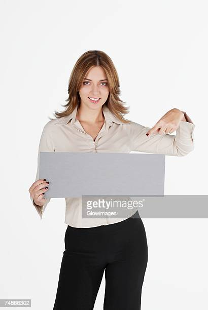 Portrait of a businesswoman pointing at a blank placard and smiling