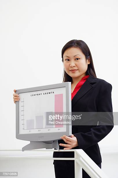 Portrait of a businesswoman showing a growth chart