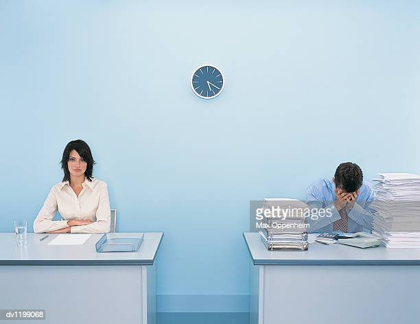 portrait of a businesswoman sitting at her desk with her arms crossed by a businessman sitting at his desk with his head in his hands - side by side stock pictures, royalty-free photos & images