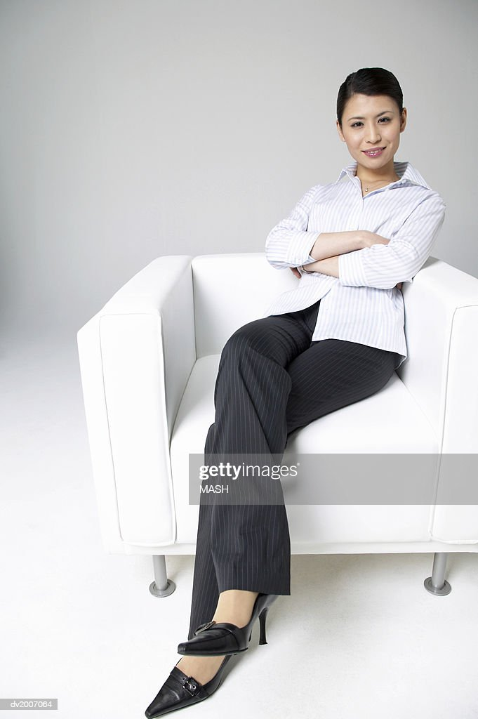Portrait of a Businesswoman Sitting in an Armchair With Her Arms Crossed : Stock Photo