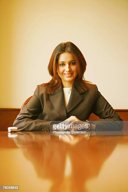 Portrait of a businesswoman sitting in an office with her hands clasped