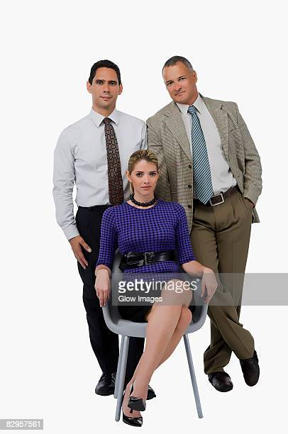 portrait of a businesswoman sitting on a chair with two businessmen standing behind her - legs crossed at ankle stock pictures, royalty-free photos & images