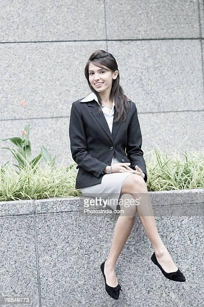 Portrait of a businesswoman sitting on a ledge
