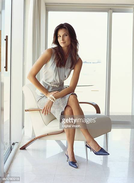 portrait of a businesswoman sitting on an armchair - bem vestido - fotografias e filmes do acervo