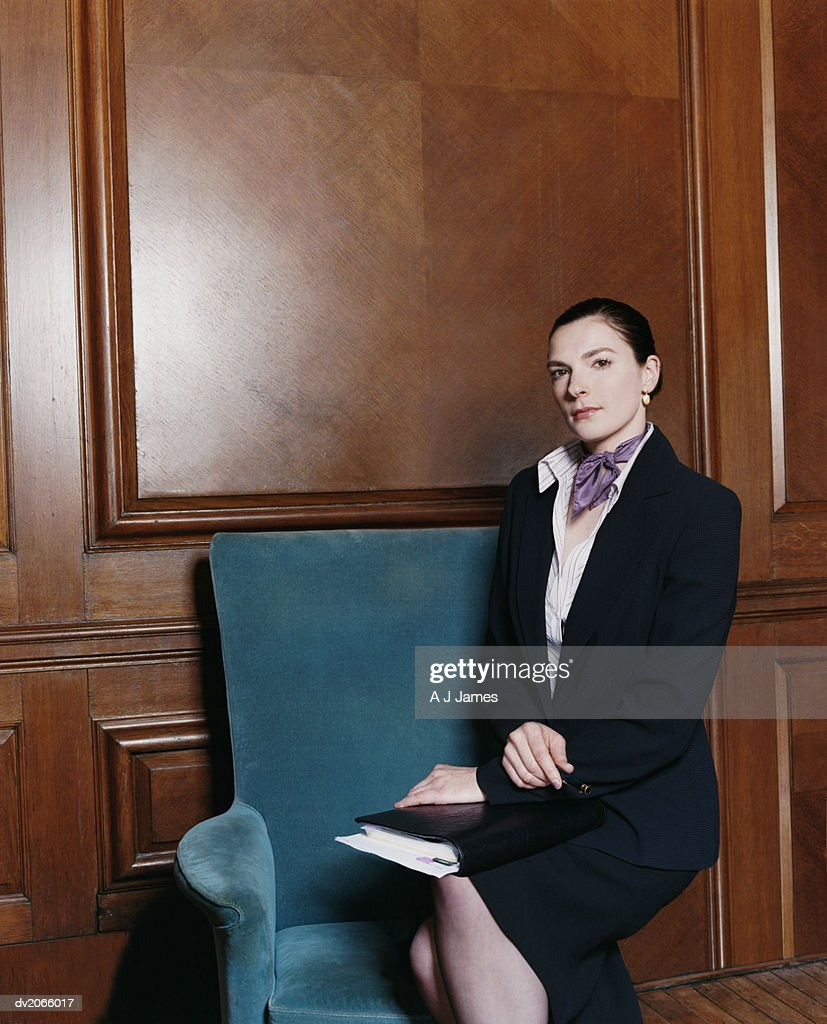 Portrait of a Businesswoman Sitting on an Armchair With a Folder on Her Lap : Stock Photo