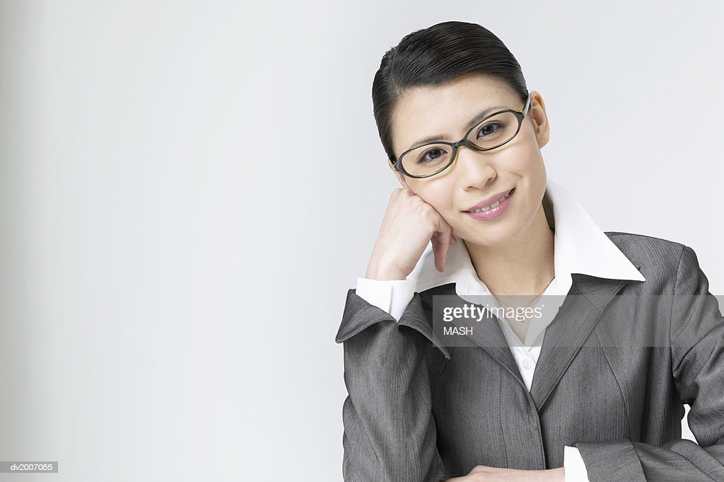 Portrait of a Businesswoman Sitting With Her Hand on Her Chin : Stock Photo