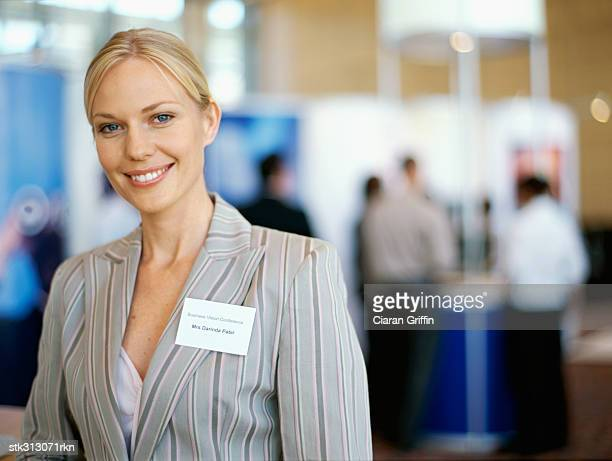 portrait of a businesswoman smiling at an exhibition - tradeshow stock pictures, royalty-free photos & images