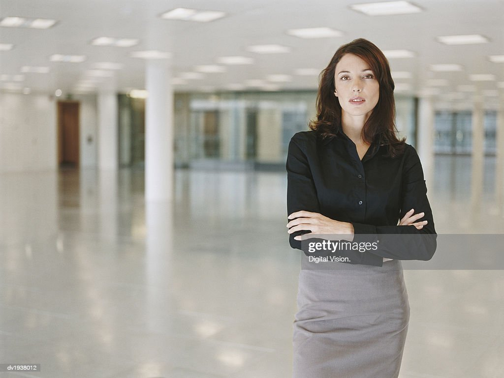 Portrait of a Businesswoman Standing in a Lobby With Her Arms Crossed : Stock Photo