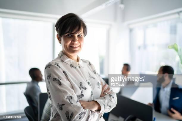 porträtt av en affärskvinna som står på kontoret med armarna korsade - positiv känsla bildbanksfoton och bilder