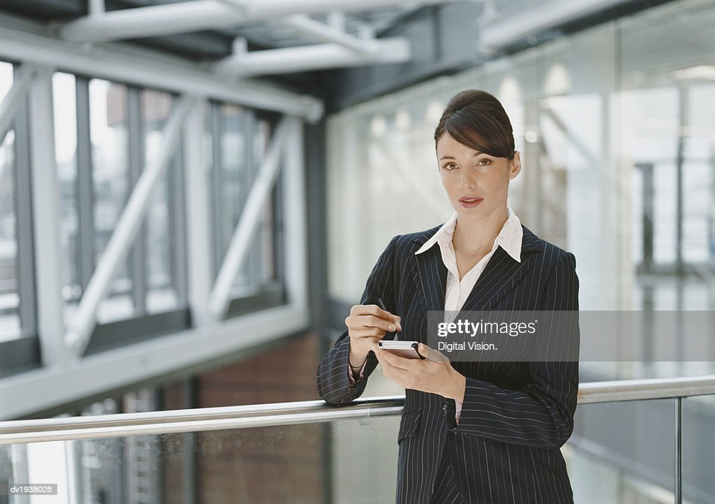 Portrait of a Businesswoman Standing on a Walkway Using a Handheld PC : Stock Photo