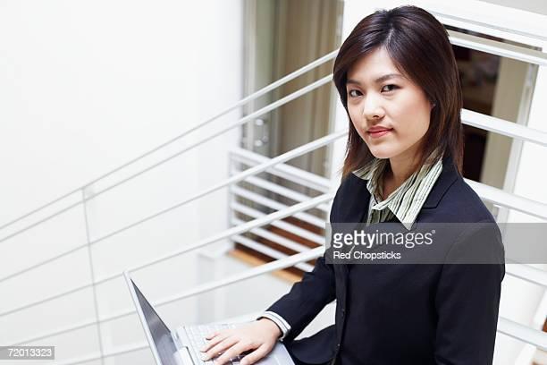 portrait of a businesswoman using a laptop - オープンネック ストックフォトと画像