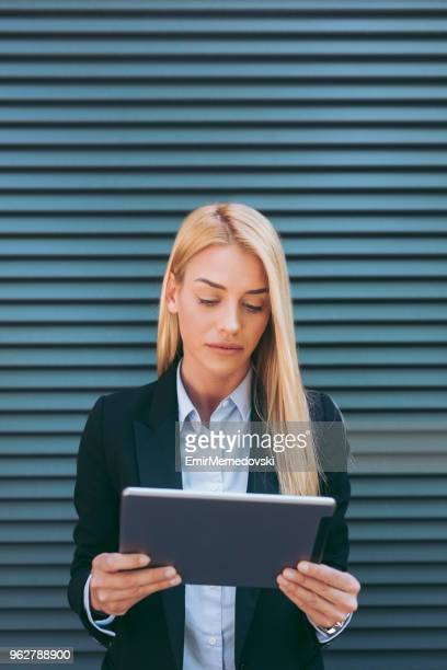 portrait of a businesswoman using digital tablet - emir memedovski stock pictures, royalty-free photos & images