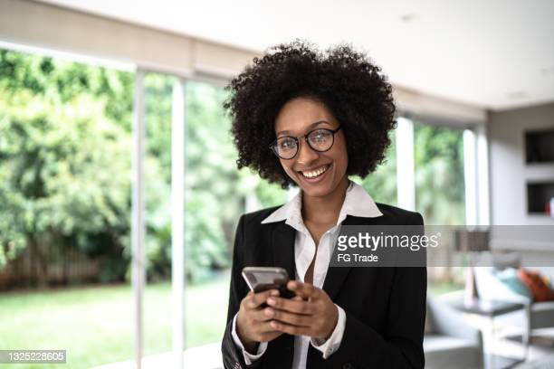 portrait of a businesswoman using smartphone at home - natural black hair stock pictures, royalty-free photos & images