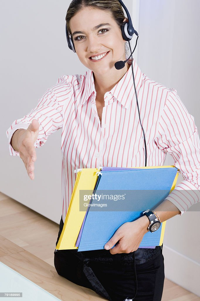 Portrait of a businesswoman wearing a headset and carrying files : Foto de stock
