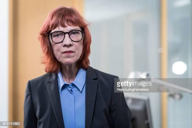 Ein Porträt einer Geschäftsfrau die kritisierend in die Kamera schaut