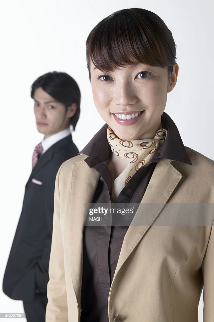 Portrait of a Businesswoman With a Businessman Standing in the Background : Stock Photo