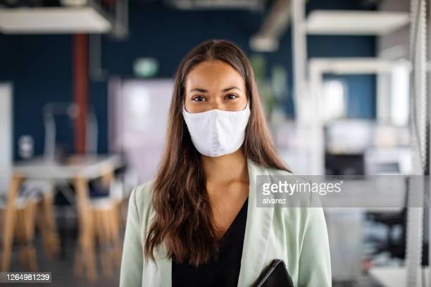 porträt einer geschäftsfrau mit gesichtsmaske im büro - abstand halten infektionsvermeidung stock-fotos und bilder