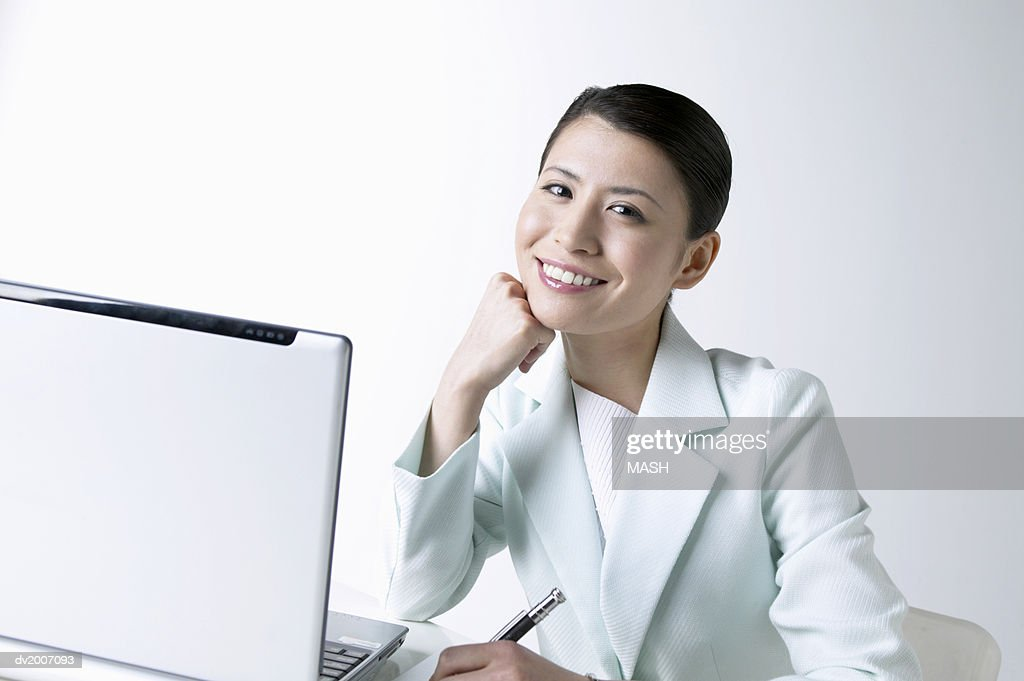 Portrait of a Businesswoman With Her Hand on Her Chin Sitting by a Laptop : Stock Photo