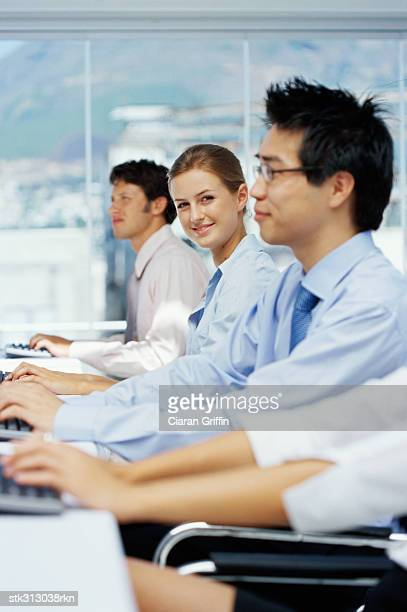 portrait of a businesswoman with three business executives using computers in an office